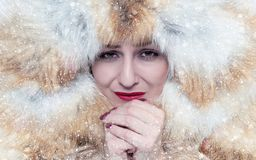 Portrait of a frozen young girl in a fox fur coat, warm her hands, cold, snow, frost, blizzard stock photo