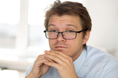 Portrait of frustrated business man wearing glasses. Businessman sitting at his office not knowing what to do. Apathy, crisis, indifference and depression Stock Images