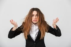 Portrait of a frustrated businesswoman dressed in suit. Pulling her hair out isolated over gray background royalty free stock image