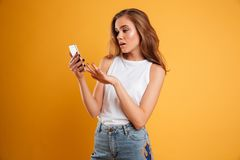 Portrait of a frustrated confused girl looking at mobile phone. Isolated over yellow background Royalty Free Stock Photo