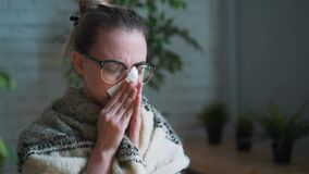 Portrait of a frustrated girl blowing her nose in a handkerchief while working with a laptop. The concept of an unhappy. Sick worker. Drinking healing tea stock video