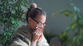 Portrait of a frustrated girl blowing her nose in a handkerchief while working with a laptop. The concept of an unhappy. Sick worker. Drinking healing tea stock footage