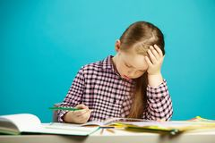 Portrait of frustrated girl at desk with textbooks, expresses fatigue and disappointment, put hand to head, puzzle over. Decision of task, sitting over blue Royalty Free Stock Photos