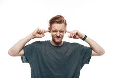 Portrait of Frustrated Man Holding Fingers in Ears stock photography