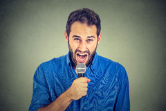 Portrait frustrated man with microphone isolated on gray wall background Royalty Free Stock Photo