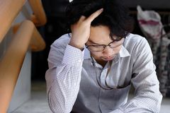 Portrait of frustrated stressed young Asian man touching head and feeling tried or exhausted. Royalty Free Stock Photos