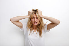 Portrait of frustrated woman pulling against white background Stock Photos