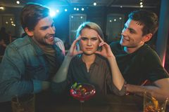 Disappointed female telling with cheerful men. Portrait of frustrated women feeling headache while listening conversation of two molesting males. Rest and Royalty Free Stock Photos