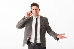 Portrait of a frustrated young businessman. Talking on mobile phone isolated over white background Royalty Free Stock Photography