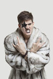 Portrait of frustrated young man in fur coat clenching teeth and making rebellious gesture against gray background Stock Image
