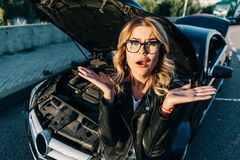Portrait of frustrated young woman with curly hair near broken car with open hood. During day stock photos