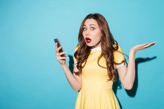 Portrait of a frustrated young woman in dress. Holding mobile phone and looking at camera isolated over blue background Royalty Free Stock Photography