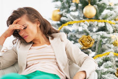 Portrait of frustrated young woman near christmas tree. In living room Royalty Free Stock Photos