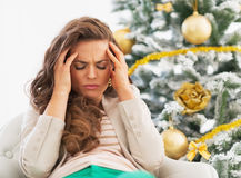 Portrait of frustrated young woman near christmas tree. In living room Royalty Free Stock Photography