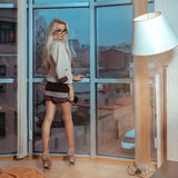 Portrait in full growth charming sexy blonde near a large window. Overlooking the city. Business woman posing. City views behind the window in the office Stock Photography
