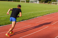 Portrait in full growth of running man on track outdoors Royalty Free Stock Photo