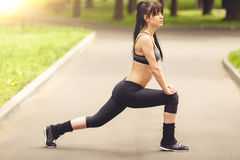 Portrait in full length of fitness young brunette stretching outdoors Stock Photo