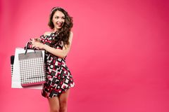 Portrait full length of happy woman holding paper shopping bag in hands and jumping, posing at camera. Wearing colored stock photos