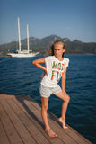 The portrait in full length of the young girl mountain and yacht behind her. The portrait in full length of the young girl about 9-12 years old with the blonde Royalty Free Stock Photography