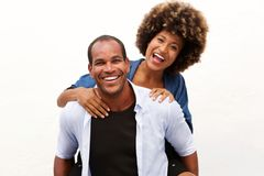 Fun couple laughing in embrace by white wall. Portrait of fun couple laughing in embrace by white wall Stock Images