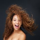 Portrait of a fun and happy young woman laughing with hair blowing Royalty Free Stock Images