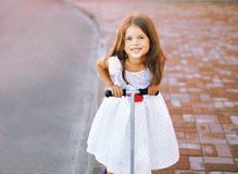 Portrait fun little joyful girl in dress on the scooter in the c Stock Image
