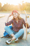 Portrait of a fun smiling young girl with skateboard and backpac Royalty Free Stock Photography