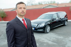 Portrait funeral director in front hearse. Portrait of funeral director in front of hearse royalty free stock photo