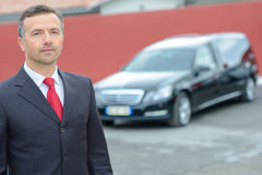 Portrait funeral director standing in front hearse. Portrait of funeral director standing in front of hearse Royalty Free Stock Photos