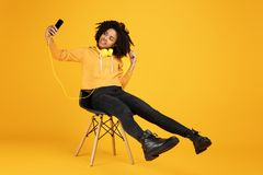 Portrait of funny african american young woman with beautiful smile dressed in casual clothes and headphones sitting on. Portrait of funny african american young royalty free stock images
