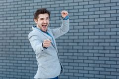 Portrait of funny amazed handsome bearded man in casual style standing, winking and pointing at camera wih happiness and excited royalty free stock photos
