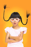 Portrait funny asian little girl with pigtail hair. Orange background Stock Photo