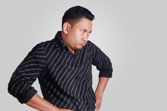 Cynical Asian Man Expression. Portrait of funny Asian man showing cynical unhappy angry facial expression, looking to the side, hands on hip,  isolated on grey Stock Photo