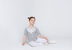 Portrait of funny astonished girl sitting on the floor on white background Stock Image