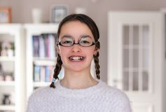 Portrait of funny attractive smiling preteen girl with pigtails and dental plates fooling around wearing glasses upside down. Havi royalty free stock photo