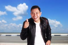 Asian man showing two thumb up. Portrait of funny attractive young Asian man in wearing black leather jacket smiling and showing thumb up sign, over cloudy blue Stock Photo