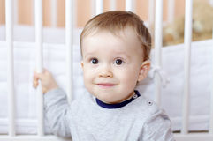 Portrait of funny baby against white bed Stock Photo