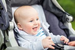 Portrait of funny baby boy laughing outdoors. Cute adorable child having fun sitting in stroller during walk royalty free stock photography
