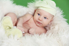 Portrait of funny baby boy resting on fur white bed Stock Photos