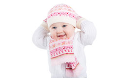 Portrait of a funny baby girl in a knitted hat, scarf and mitten. Isolated on white royalty free stock image