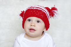 Portrait of funny baby in red knitted hat Royalty Free Stock Photo