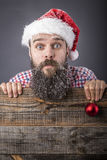 Portrait of a funny bearded man with santa cap holding a red dec Stock Photos