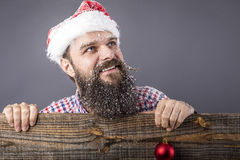 Portrait of a funny bearded man with santa cap holding a red rou Royalty Free Stock Photography
