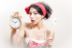 Portrait of funny beautiful brunette woman pinup girl wearing apron holding alarm clock and spoon in hand, looking at camera Stock Photos