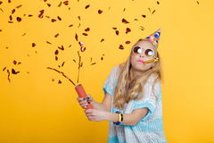 Portrait of funny blond woman in birthday hat and red confetti on yellow background. Celebration and party. Royalty Free Stock Image