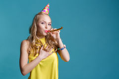 Portrait of funny blond woman in birthday hat and yellow shirt on blue background. Celebration and party. Royalty Free Stock Photo