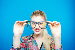 Portrait of Funny Blonde Woman with Ponytail Wearing Colorful Shirt and Fashionable Eyeglasses on Blue Background. Portrait of Funny Blonde Woman with Ponytail Stock Images