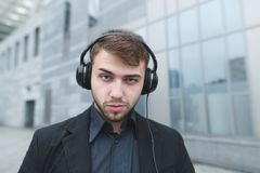 Portrait of a funny businessman with a beard and headphones on the head that lays on the camera against Stock Photography
