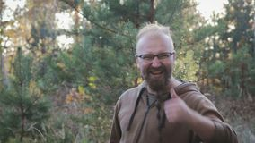 Portrait of a funny, cheerful man with glasses and a beard in the shape of a pigtail. Man raises his thumb up and shows stock video