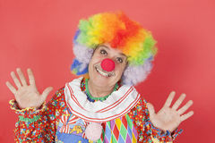 Portrait of funny clown with arms raised against colored background Royalty Free Stock Photography